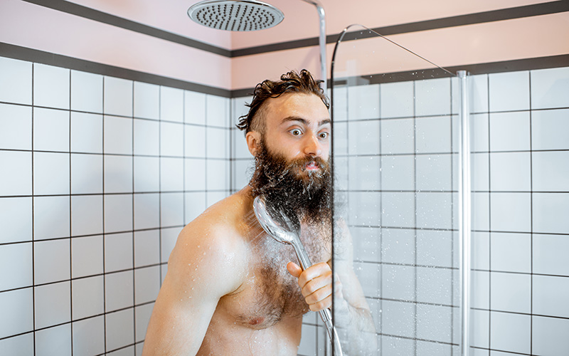 A white man with brown hair and a long brown beard stands topless in a glass-walled shower. He holds the shower head to his right shoulder. His eyes are spread wide in an expression of shock as if he has just been hit by the first jets of cold water.