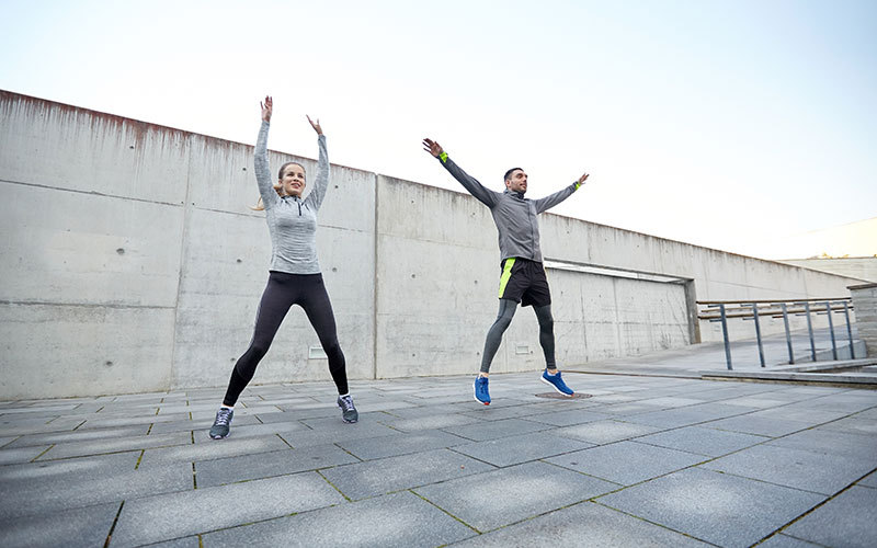 A white woman and white man do jumping jacks on a concrete plaza outdoors
