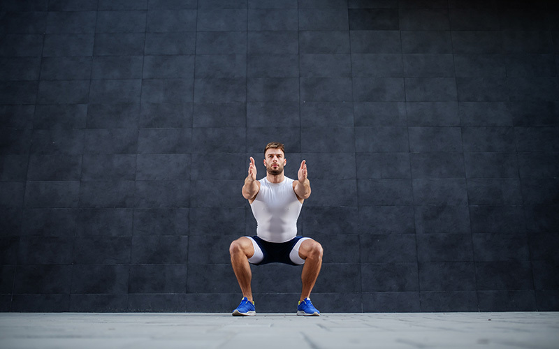a white man doing an air squat with his own body weight in front of a gray marbled wall