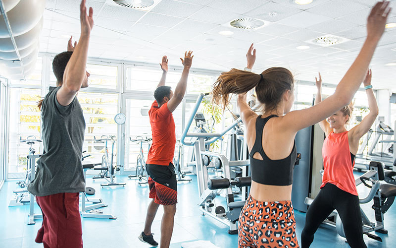 A group of mixed genders and races does jumping jacks in a gym surrounded by weights machines