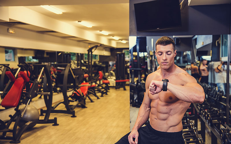 A white athlete checks his smartwatch during a break from natural bodybuilding. He is standing in a gym and is shirtless.