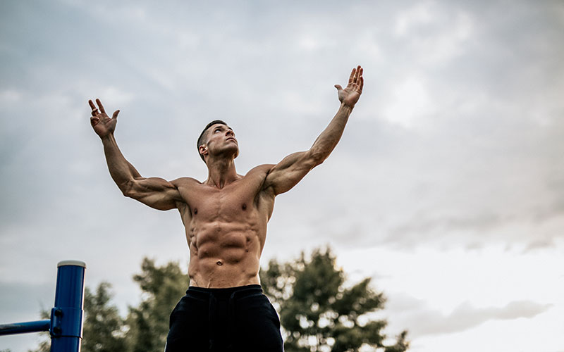 A shirtless white man shows off his muscles outdoors in front of a cloudy sky