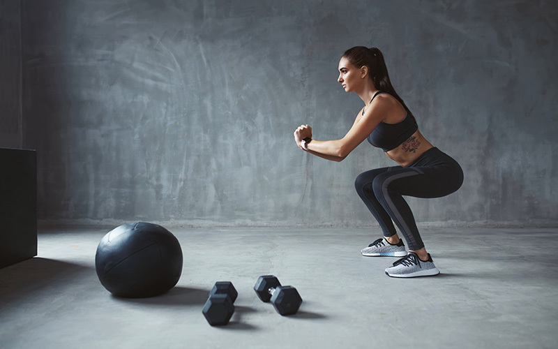 A white woman does squats with a weighted ball and two dumbbells in front of her.