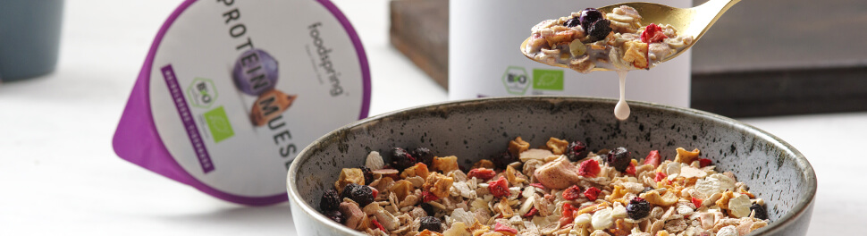 A drip of milk falls from a spoon loaded with colorful and healthy organic protein muesli by foodspring.