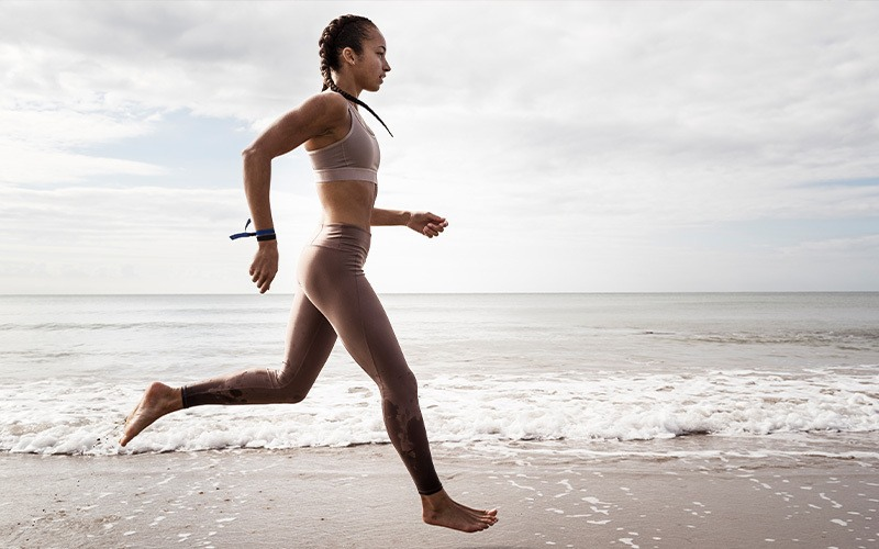 how to lose weight without dieting? the simplest is exercise, as shown by this medium-skin-toned woman running on the beach with waves breaking near her bare feet.