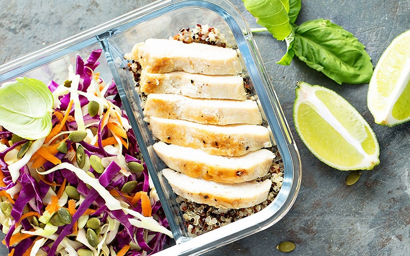 A glass food storage box holds a meal with quinoa topped with sliced chicken breast on one side of its divider while the other side has sprouts and shredded salad. On the side is lime quarters.