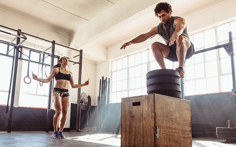 A white woman jumps rope while a man with curly brown hair does a box jump in a gym. They appear to be doing a couple workout of different activities.