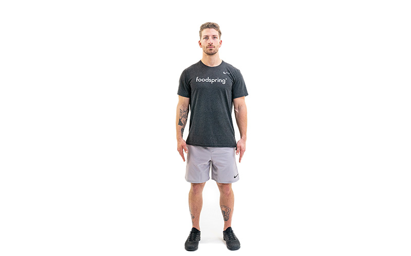 A white man in a black foodspring t-shirt and athletic shorts shows the starting position for jumping jacks. He stands with feet shoulder-width apart and arms down at his sides.