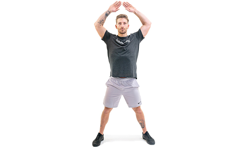 A white man in a black foodspring t-shirt and athletic shorts shows the ending position of a jumping jack. His feet are spread and on the floor. He holds his hands about 10 cm over his head, elbows bent, hands extended with fingertips 2 cm apart.