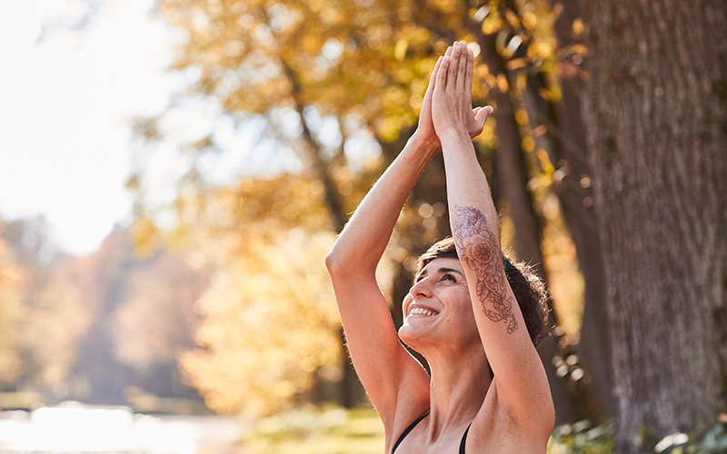 A woman touches her hands together flat over her head while outdoors in the forest