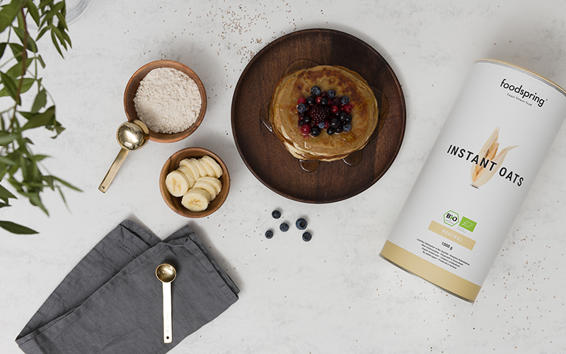 A package of foodspring's Instant Oats with pancakes, sliced bananas, and scoop as seen from above