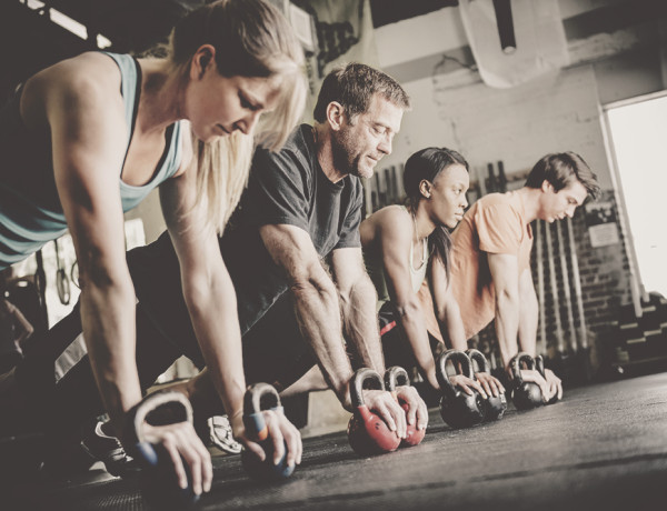Gemischte Trainingsgruppe macht Kettlebell-Pushups