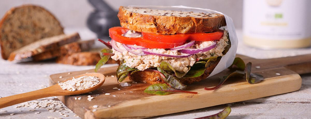 tuna sandwich loaded with tomato slices, red onion, and baby Swiss chard leaves