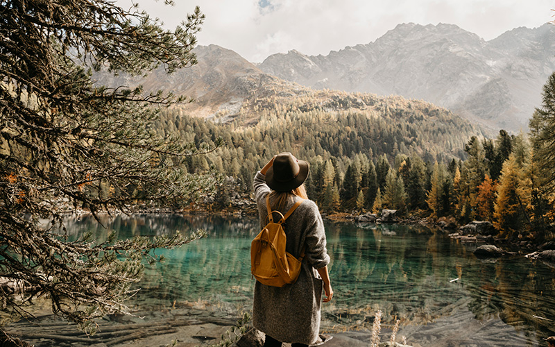 A white woman with a felt hat looks out at a mountain lake surrounded by forest