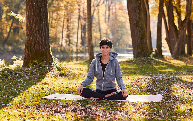 A short-haired white woman sits on a yoga mat in the forest.