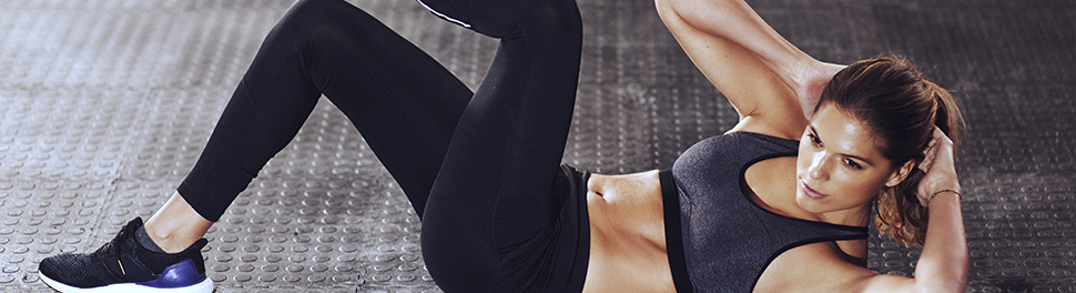 A white woman in a sports bra and black leggings performs an oblique bending crunch.