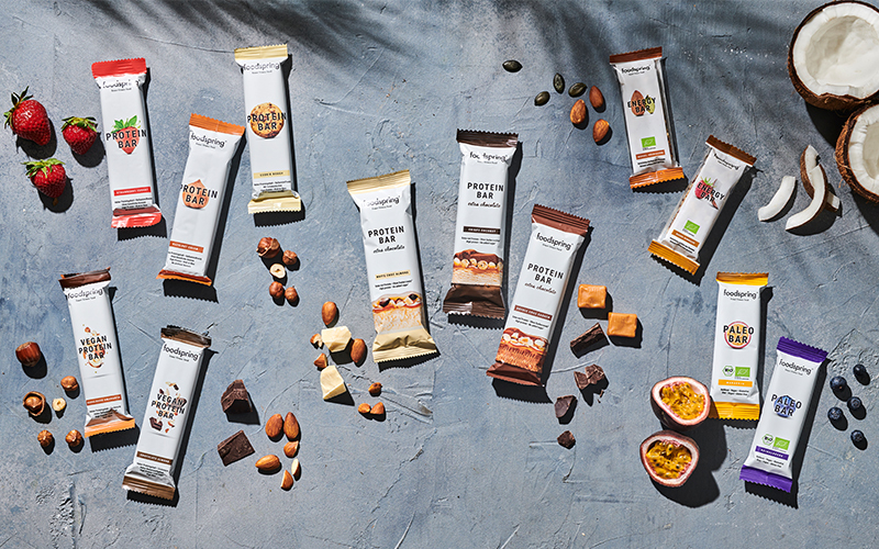 A selection of foodspring's best energy and protein bars laid out on a gray background with ingredients such as nuts, chocolate chunks, and caramel strewn artistically around them.