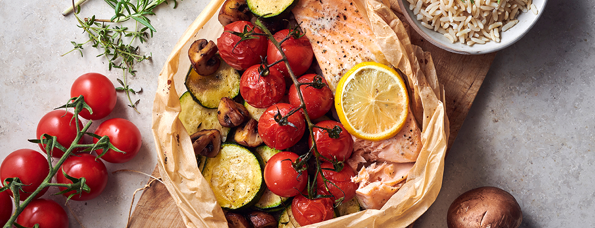 a parchment-paper parcel of salmon with a lemon slice on top and cherry tomatoes on the vine, zucchini rounds, and quartered cremini mushrooms next to it