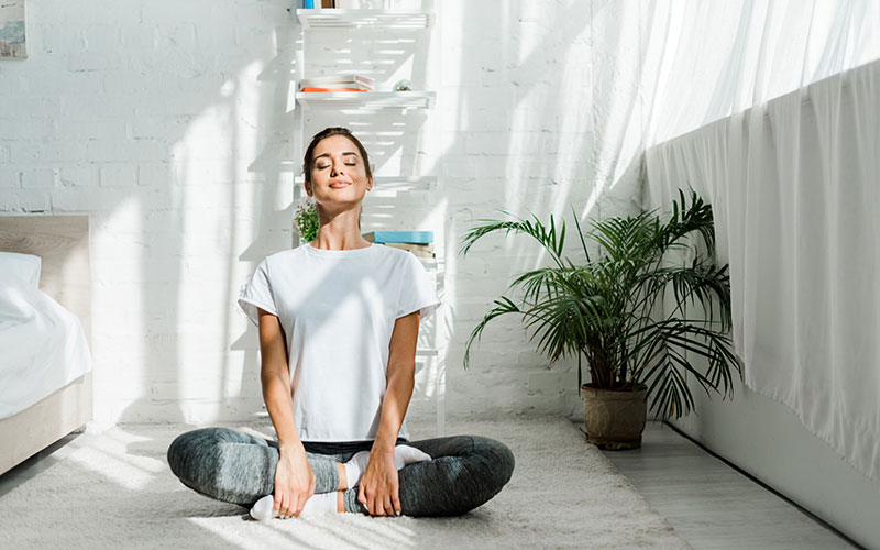 photo of a white woman in a bedroom meditating to develop healthy habits
