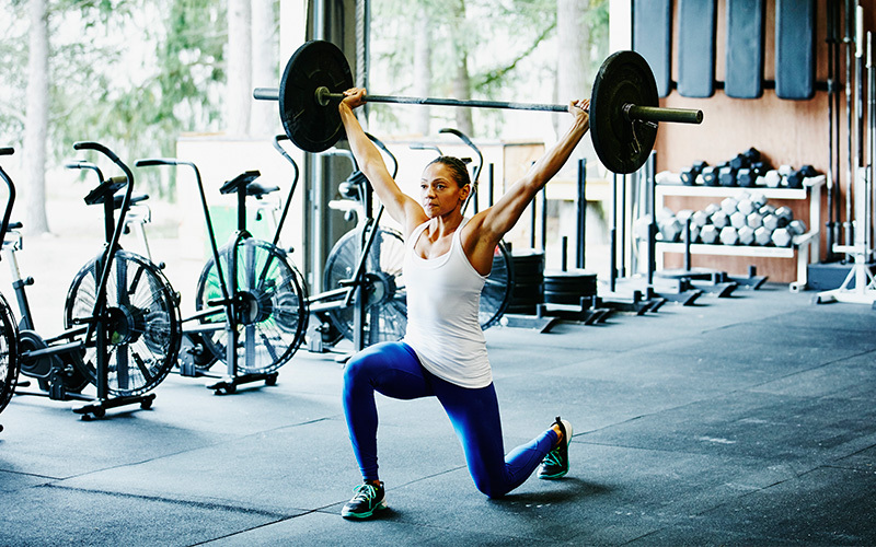 frau macht barbell lunges