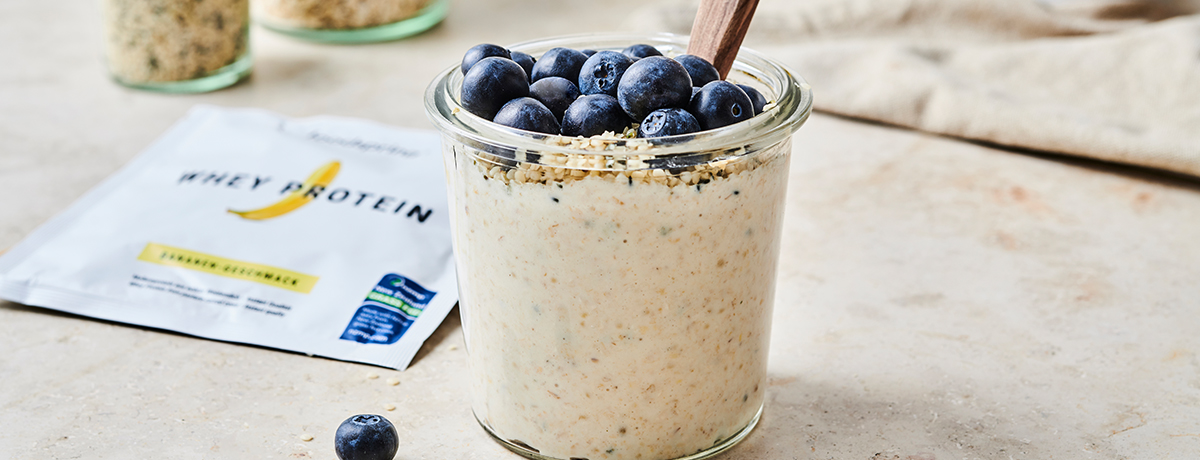 a glass jar of overnight oats topped with fresh blueberries sits next to a single-serving package of foodspring's banana Whey Protein