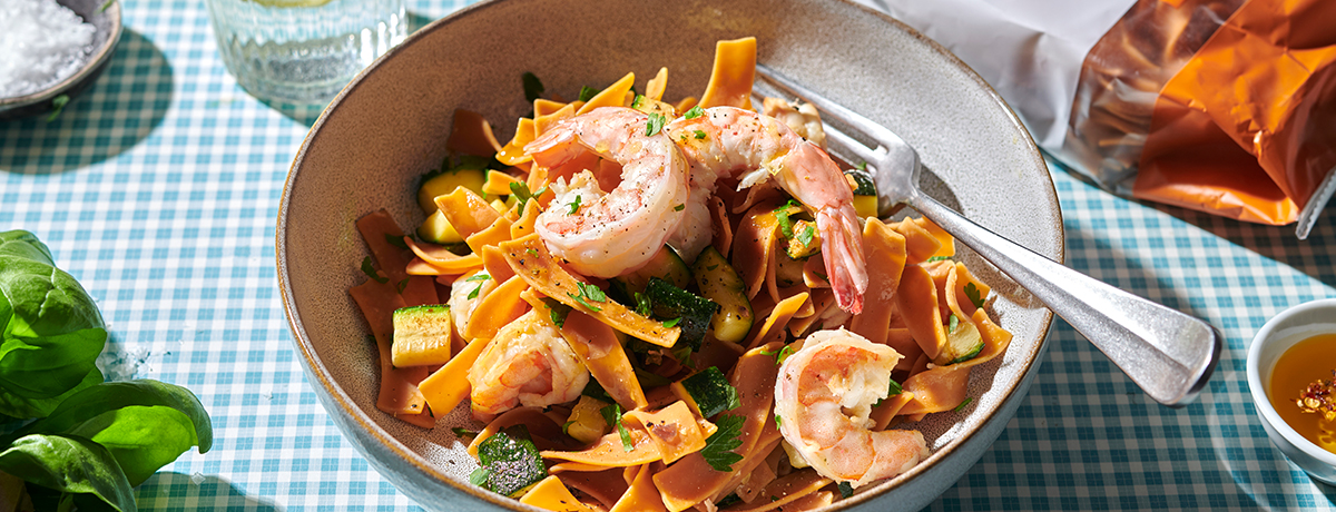 photo of a plate of pasta fredda with orange noodles and pink shrimp, garnished with green leaves