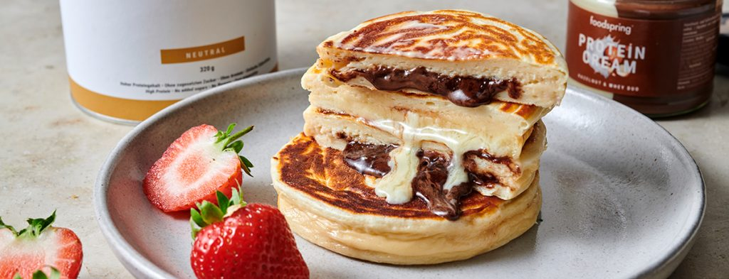 a stack of Protein Pancakes dripping melted Protein Cream