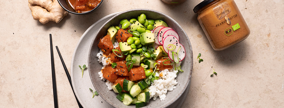 a poke bowl with salmon, and a jar of Organic Peanut Butter on the side