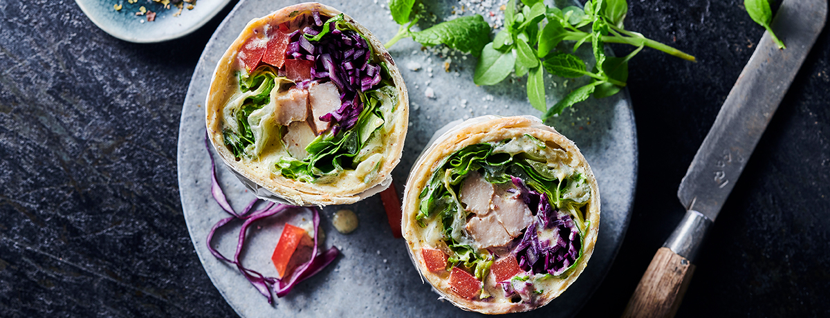 A photo of a wrap filled with chicken and vegetables, one of foodspring's recipes. Check out our recipes section for delicious ways to build healthy habits.