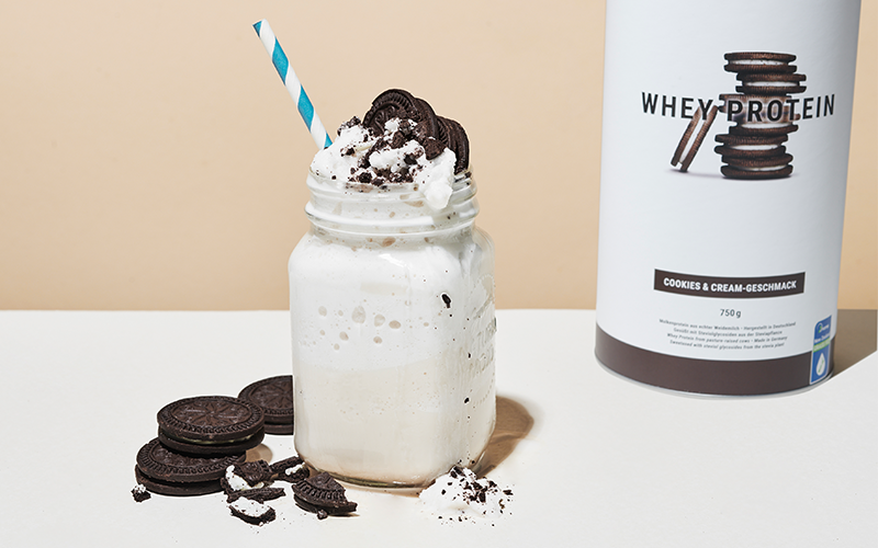 A Mason jar of white Whey Protein topped with white whipped cream, crumbled chocolate sandwich cookies and a blue-and-white-striped paper straw sits next to a canister of Cookies & Cream flavored Whey Protein by foodspring