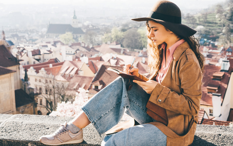 A woman of color sits on a barrier wall with an overview of the red, pointy roofs of a European town behind her. She writes a WOOP method plan in her journal, which balances on her knee.