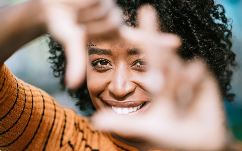 A woman of color looks through a square formed by her fingers, giving a big smile to the camera.