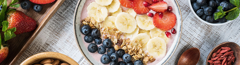 a photo of a bowl of yogurt topped with fresh berries, granola and banana slices