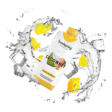 CocoWhey packaging in the midst of flowing water and mango chunks
